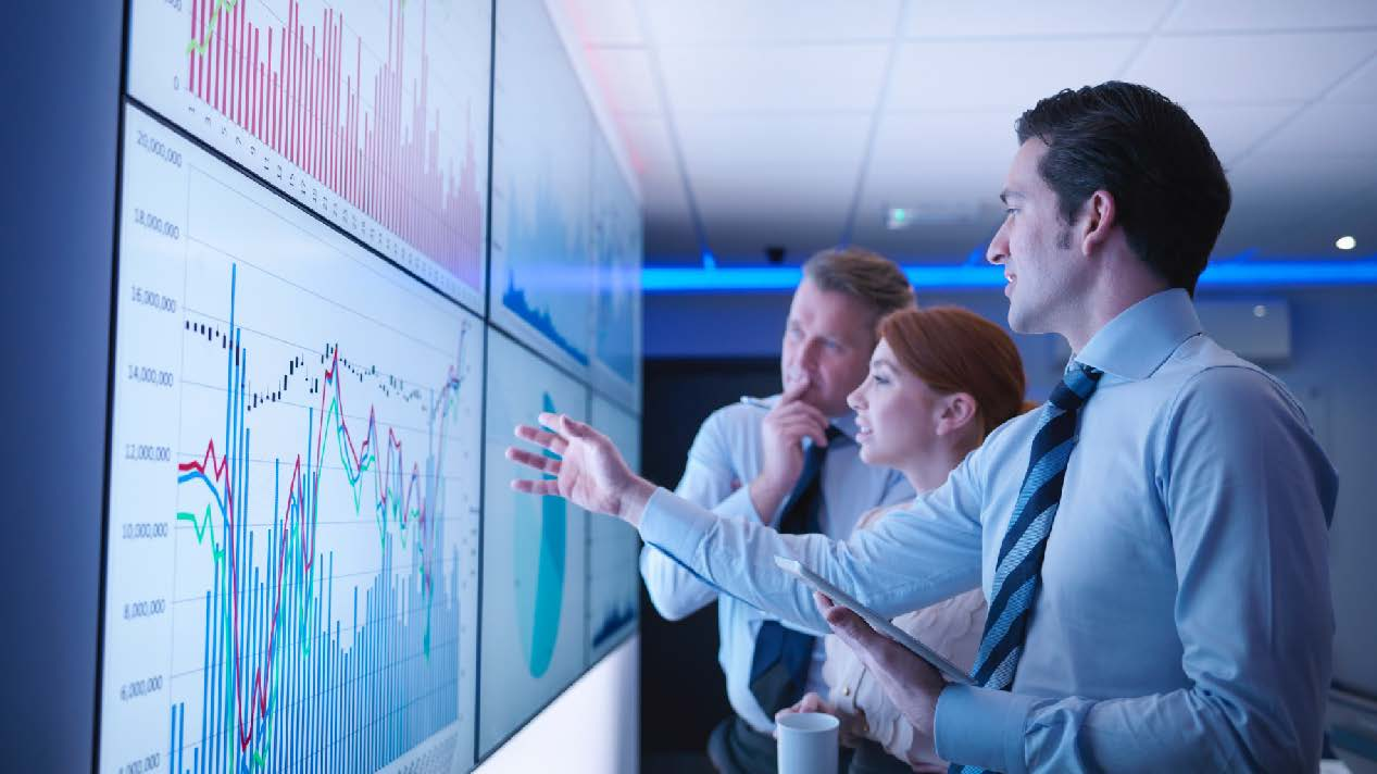 Three professionals looking at a stock chart on a large screen