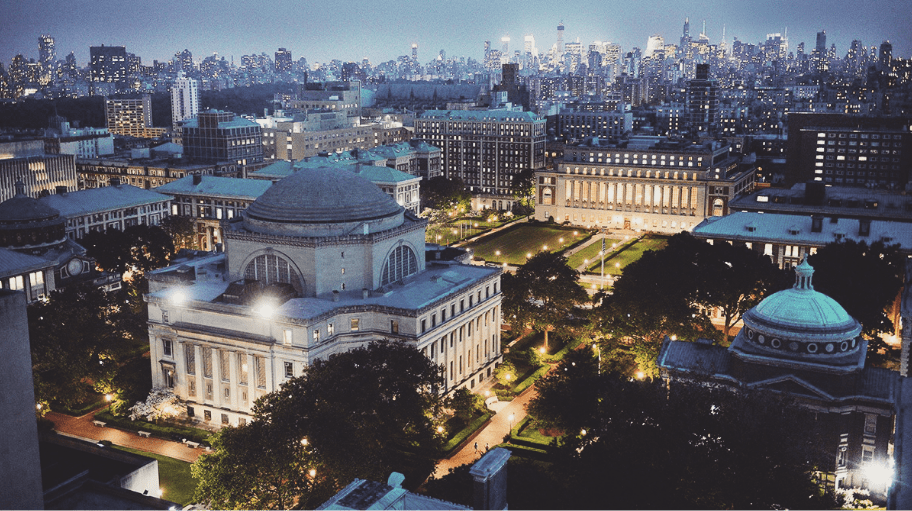 Aerial view of the Columbia University campus at night with view of New York City skyscraper off in the distance..