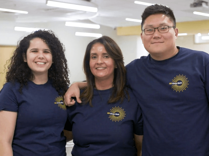 Three AB employees smiling at a volunteer event