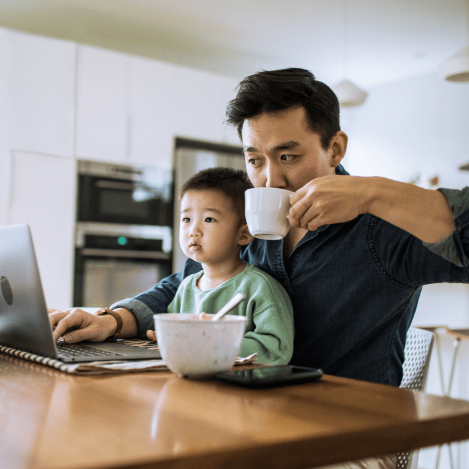 Asian father and toddler son sitting at home office in front of a computer